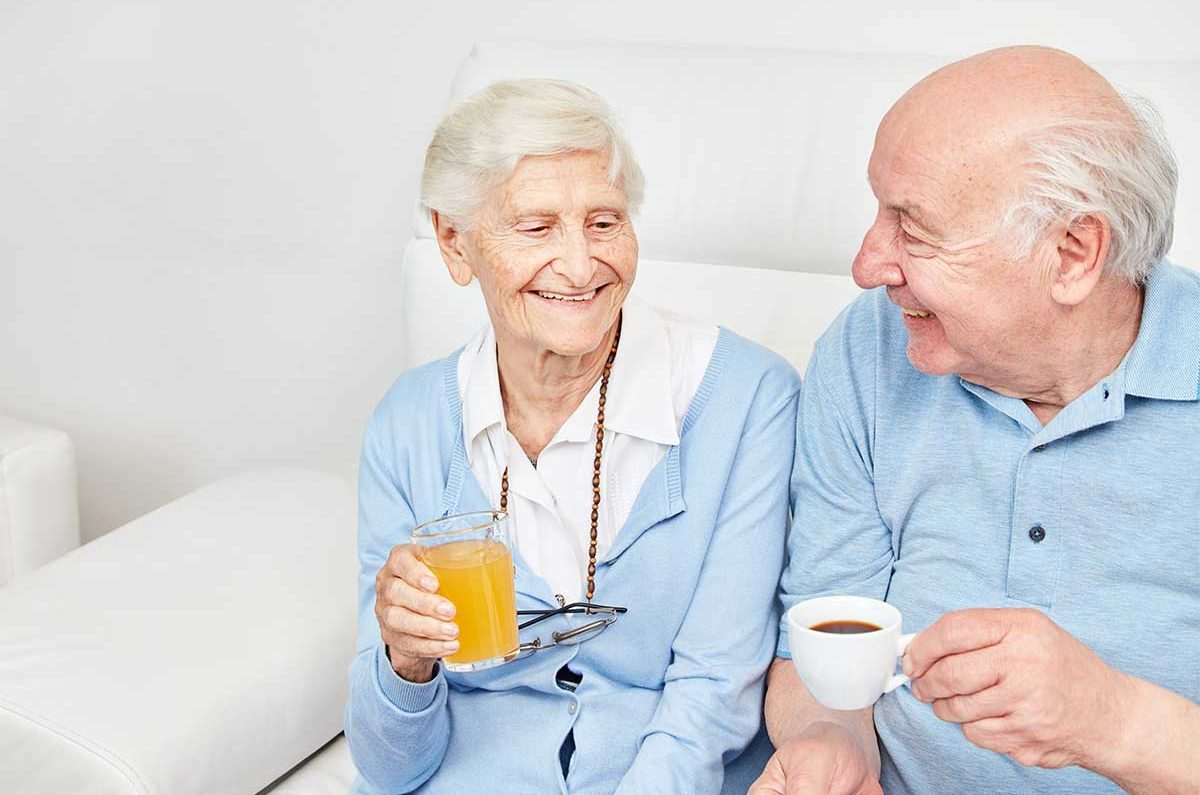 Happy smiling senior couple dinrking coffee and juice