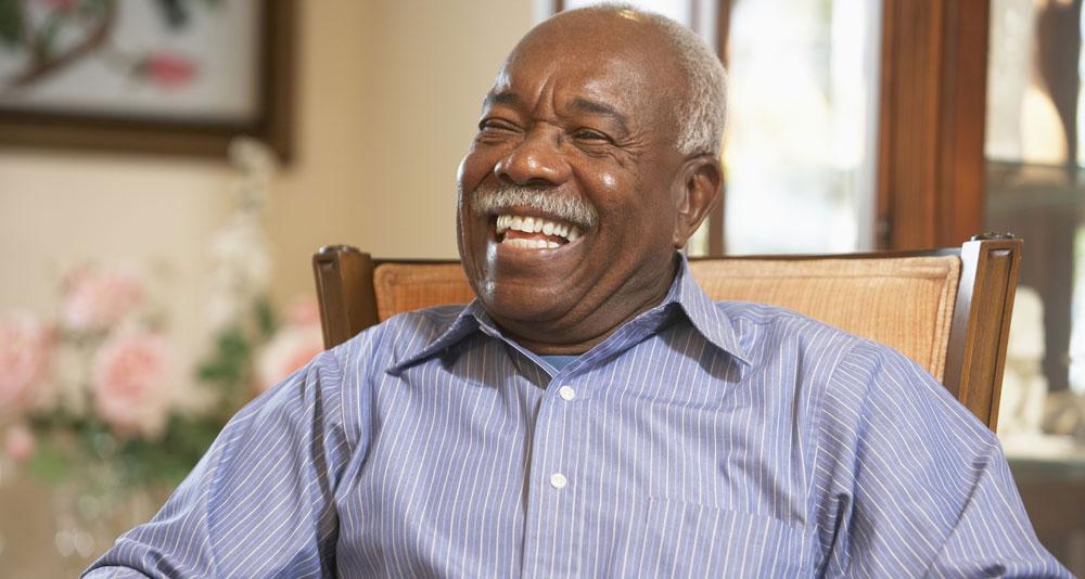 Happy Senior Man sitting in armchair grinning